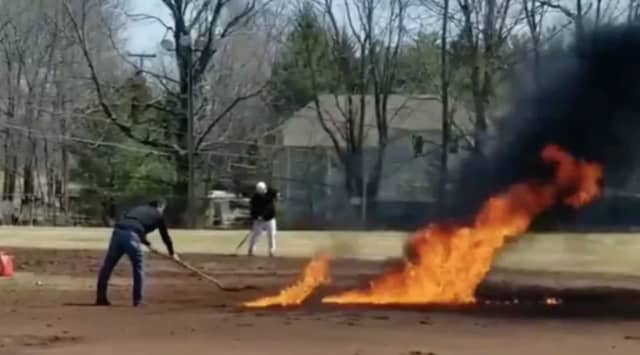 Three coaches in Ridgefield have been suspended after attempting to dry a field by lighting it on fire.