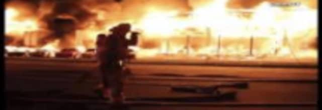 A firefighter battles the intense blaze at a car dealership where an HBO mini-series was filming.