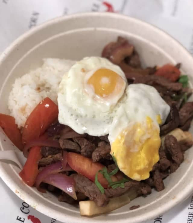 Lomo Saltado Moltado (Beef over rice and fries with tomatoes and fried egg) from Purple Corn Peruvian Rotisserie Joint, located at 72 Mamaroneck Avenue.