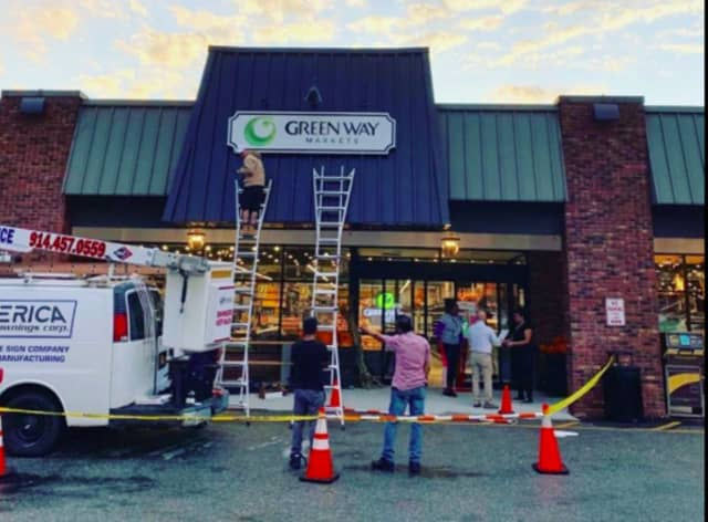 The sign for the Green Way Market opening in Cross River goes up.