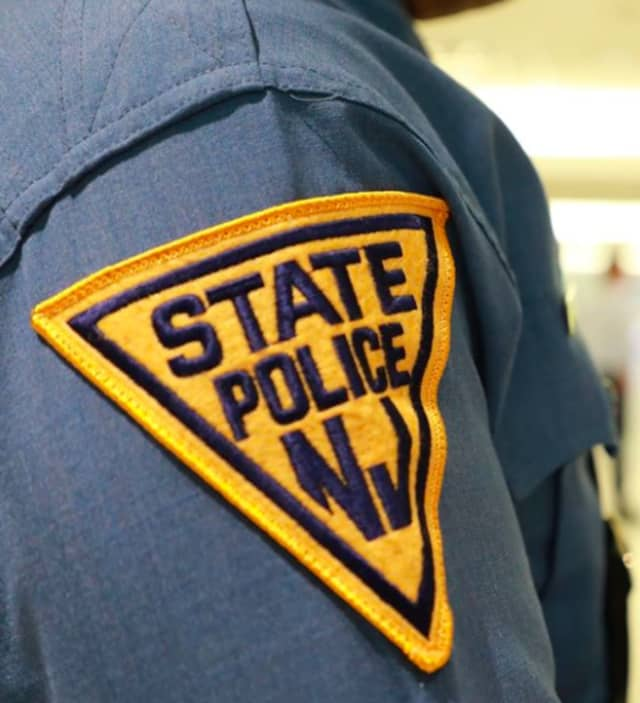 A New Jersey State Trooper was hospitalized with minor injuries after his parked car was slammed by an Audi on the Garden State Parkway, authorities said.