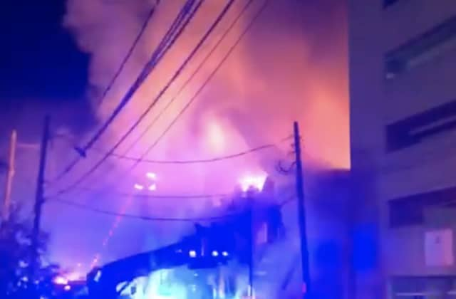 A four-alarm fire heavily damaged several apartments and businesses on Long Island.