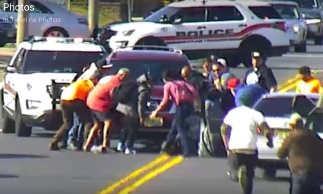 More than a dozen bystanders ran to help Neptune Township police rescue a bicyclist trapped under an SUV.