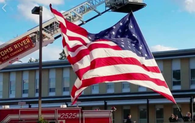 Members of Toms River Fire Department No. 1 hoist an American flag outside Community Medical Center.
