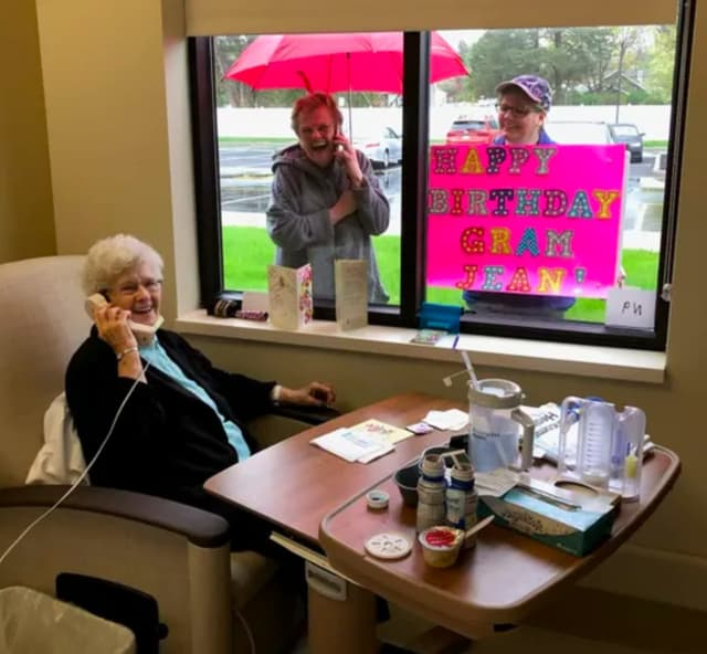 Jean Powell (seated, on phone) speaks with daughter Kim Wedemeyer (top left) and granddaugther Shaylin Bell (top right) on her 91st birthday, after beating COVID-19 (Photo: Encompass Health Rehabilitation Hospital of Toms River)