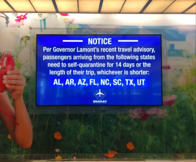 A sign at Bradley Airport in Windsor Locks, Connecticut announced the first quarantine order on June 25, which included the eight states shown.