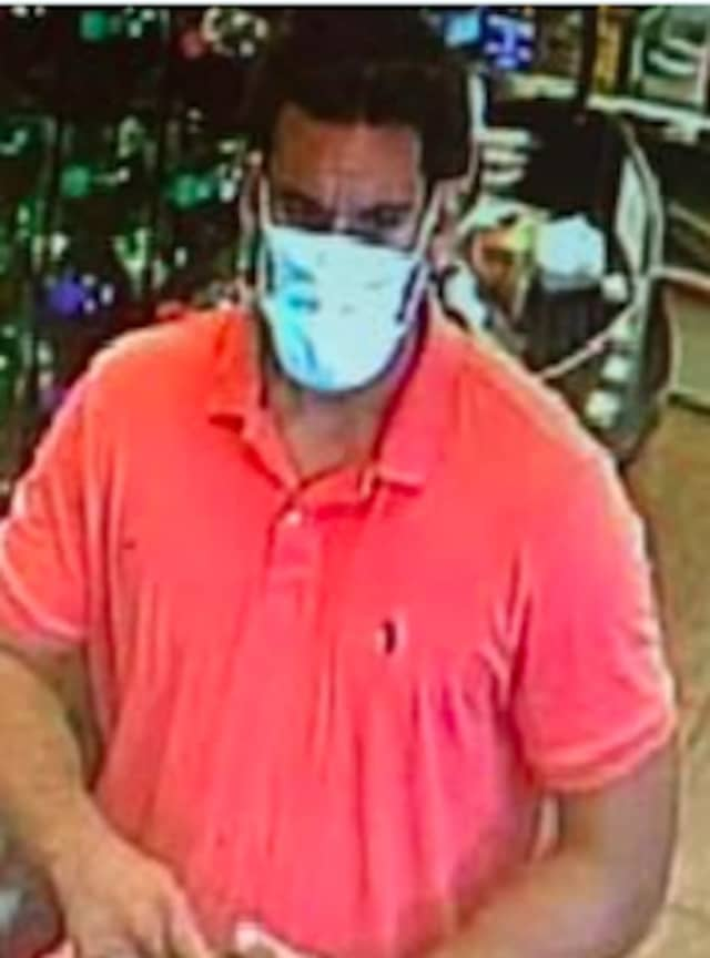 Surveillance footage of a man who stole a Rolex watch and awallet containing credit cards from a vehicle.