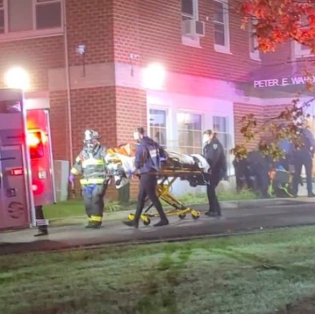 First responders carry a fire victim from an apartment building at 100 Woehr Ave. in Lakewood.