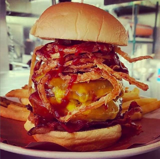 """A double """"Better with Cheddar"""" burger, topped with sharp cheddar cheese, crispy bacon, smoky BBQ sauce and frizzled onions."""