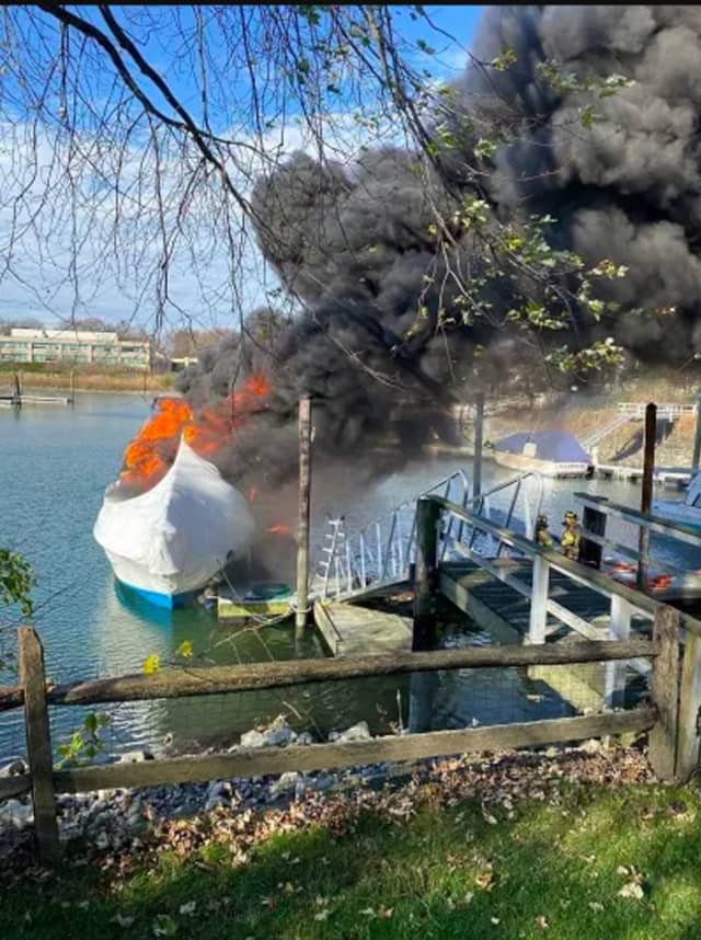 The 38-foot cabin cruiser located at a dock behind 109 Dolphin Cove Quay well-involved in flames.