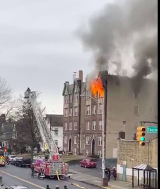 Flames shot out of the 4-story building at 118 West 2nd Street, as firefighters from surrounding areas arrived around 11:15 a.m.