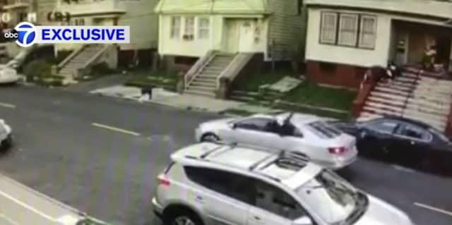 In this video still, someone with a gun is seen firing  at a Newark house through the back window of a car Wednesday. A young girl was wounded in the incident.