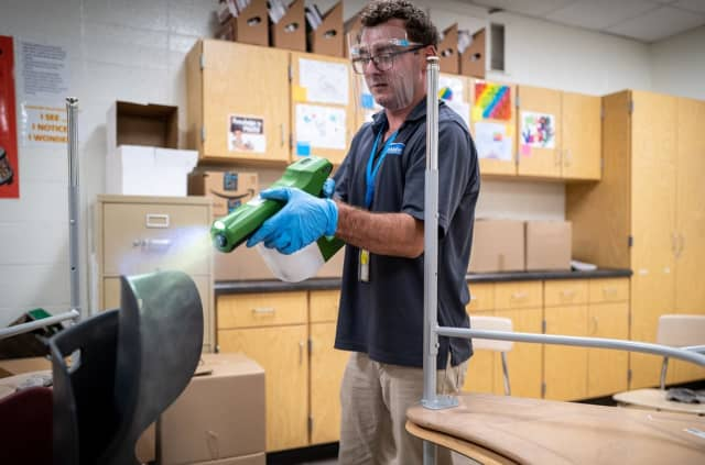 A man sprays disinfectant on school equipment.