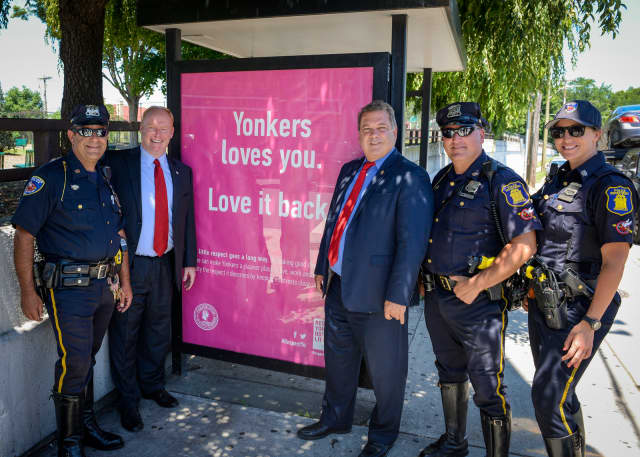 City Council President Liam McLaughlin, Mayor Mike Spano and local police officers show off one of the new anti-littering signs.