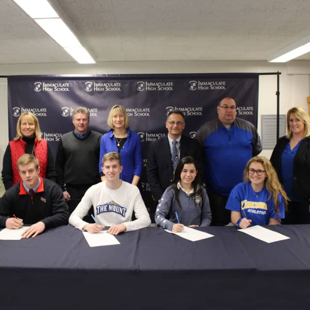 Will Hatcher, Sean Fahey, Danielle Marcone and Kayla Lanza sign National Letters of Intent to play college sports in the fall. All are seniors at Immaculate High School in Danbury.