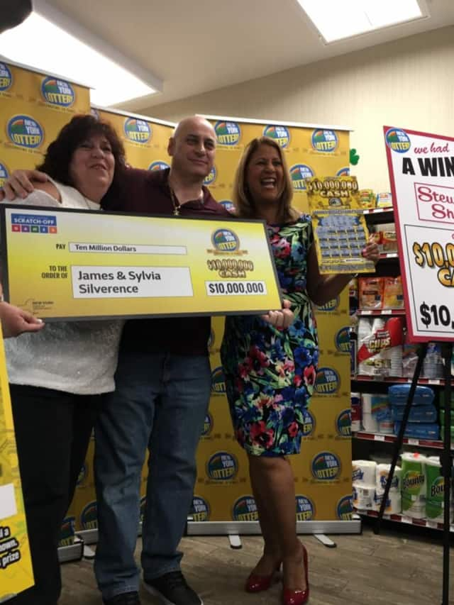 Poughkeepsie couple James and Sylvia Silverence accept an oversized check for $10 million from Lottery spokeswoman Yolanda Vega at a Stewart's Shops store Thursday.