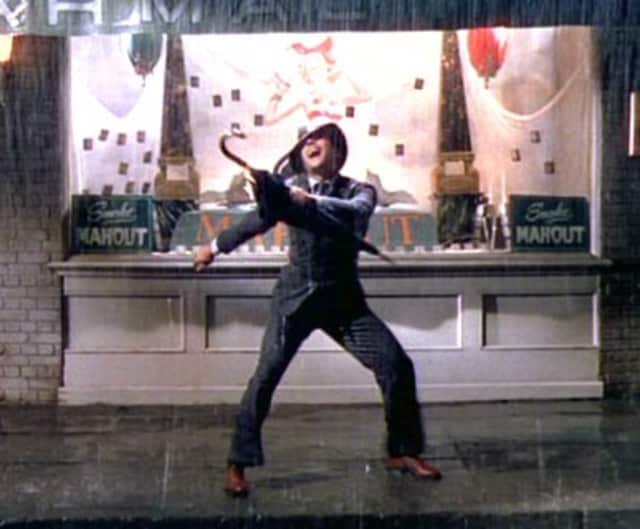 """Gene Kelly dancing while singing the title song """"Singin' in the Rain."""""""