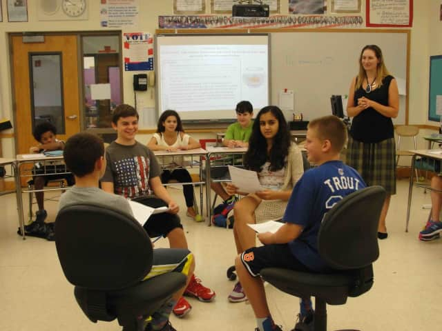 Seventh-graders, who examined Native American artifacts from various cultural areas during a unit on Native Americans, discuss with their peers whether or not Americans today value the environment equally.