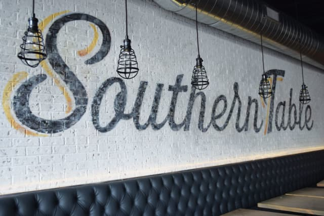 Southern Table features industrial fixtures and brick walls.