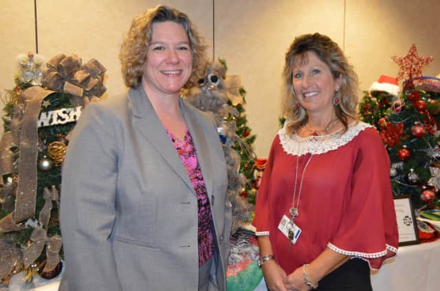 Susan Agamy, executive director of Spooner House, left, joined Kim Hall, senior applications coordinator at Griffin Hospital in picking winners in the tree raffle.