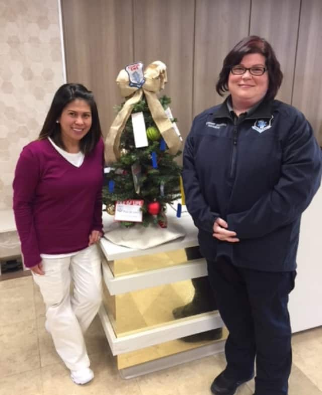Simonette Castaneda, Regional MDS Director for Cassena Care of Stamford accepts a donated tree from Jessica Anderson, Stamford EMS Lieutenant and Academy Training Coordinator, for the fourth annual Festival of Trees