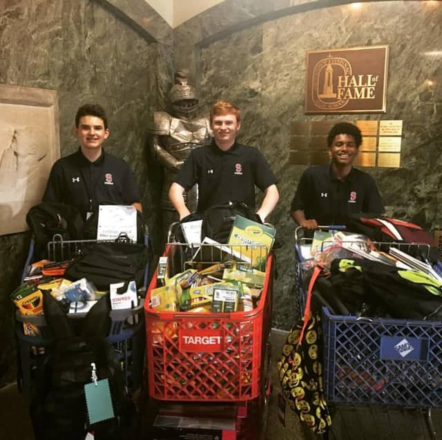 Freshman Devlin Hose, senior John Skelton and sophomore Tyler Stewart display some of the many school supplies they and their fellow students collected to help a high school classroom in Texas that had been impacted by Hurricane Harvey.