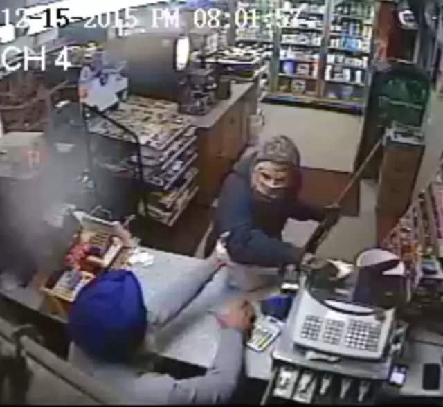 Gas station attendant struggles with suspect.