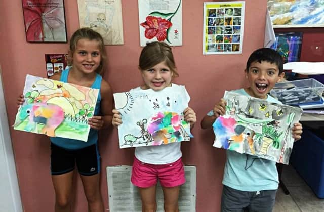 Students from the studio's summer camp show off their art.