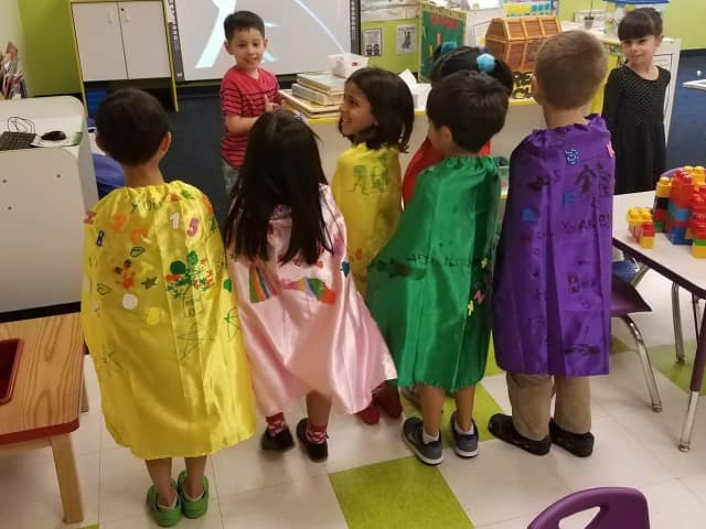 Preschoolers at The Learning Experience show off the capes they made for kids at local hospitals.