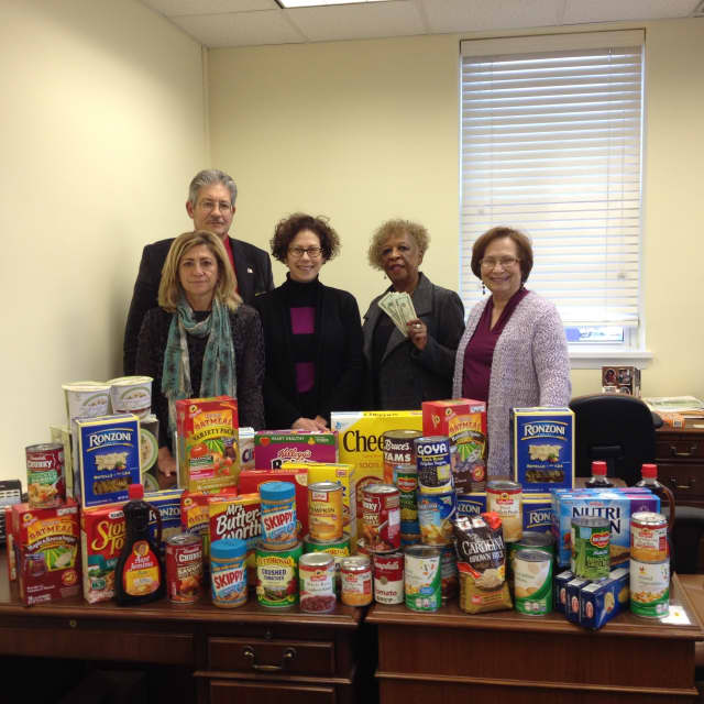 Judith Giordano (far right) and some of the food that was collected along with sales associates Jim Efron, Roula Savva, Susan Levinson and Beverly Mitchell, event chairperson.