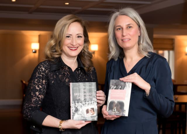 """Nyna Giles (black lace) and Eve Claxton (blue dress) with copies of their book """"The Bridesmaid's Daughter."""" Photograph by Lynda Shenkman."""