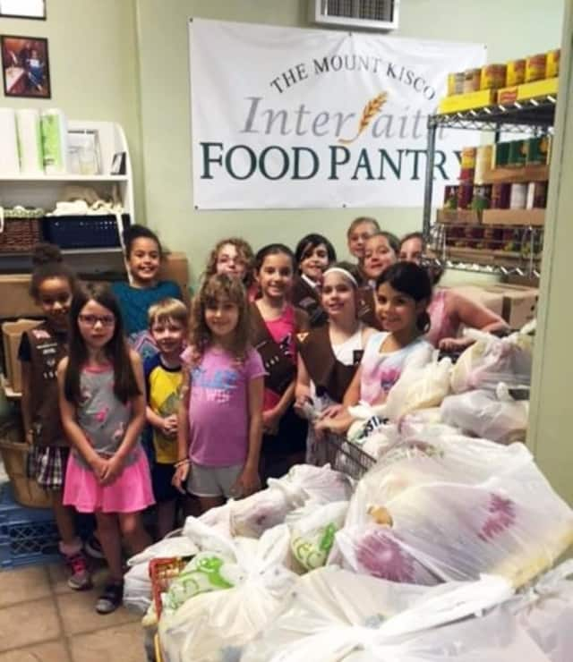 Folks from throughout the area support the Mount Kisco Interfaith Food Pantry -- even without fines. The Girl Scouts of Bedford Troop 1443 helped pack bags of produce this summer.