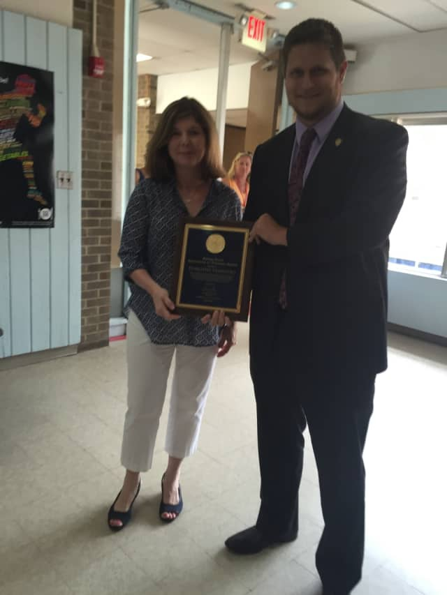 West Patent Elementary School teacher Dorothy Venditto, left, gets an Excellence In Teaching award from Thomas Scaglione, a representative of Gov. Andrew Cuomo.