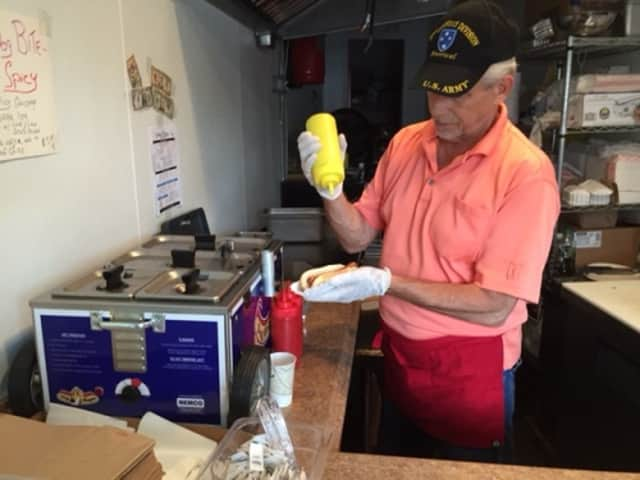 Eugene Parrotta puts a little mustard on a dog at Three Dog Bite, his restaurant on Grand Street in Croton-on-Hudson.
