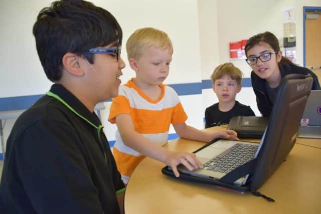 Fifth-graders at Todd Elementary School share their coding knowledge with kindergartners.