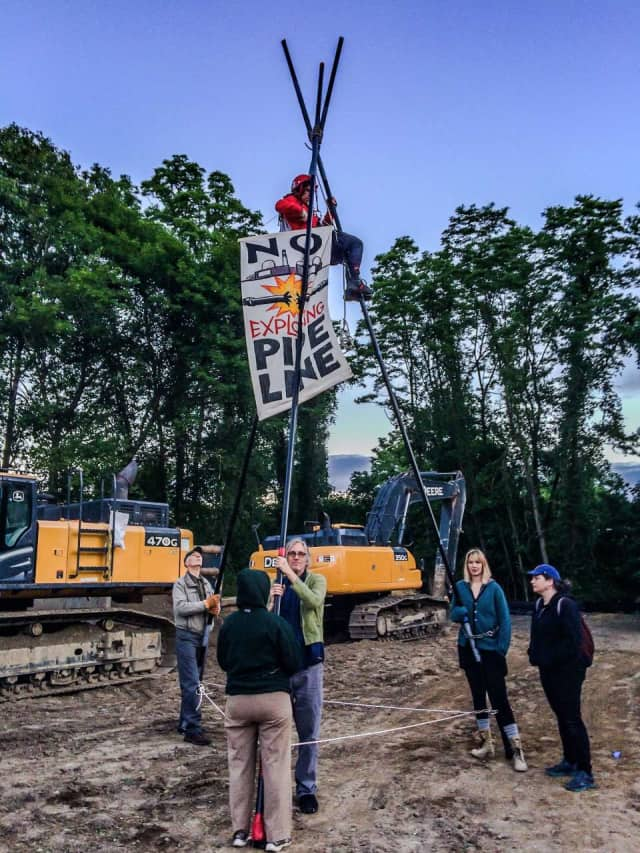 A protester climbed up a 20-foot tripod to oppose construction of the Spectra pipeline.