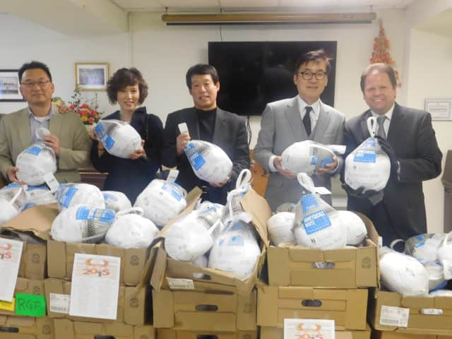 Leem's Corporation officials and Mayor James Rotundo, far right, distribute turkeys to seniors in Palisades Park on Monday.