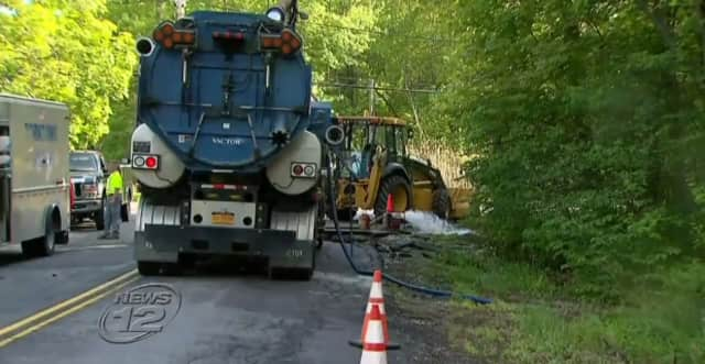 Gushing water from a water main break leaves a big hole on Greenwood Street in Yorktown, News 12 says.