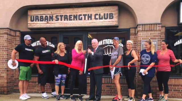 State Rep. Brenda Kupchick (third from left), First Selectman Mike Tetreau and Urban Strength Club Owner Debbie O'Toole (with scissors) are joined by staff, friends and well-wishers at an official ribbon cutting ceremony.