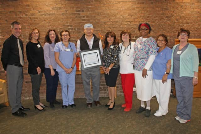Brad Sherwood, Regional Director of Business Development for VOHRA Post-Acute Physicians, Dr. Dennis Ng and members of Waveny Care Center's clinical team with an award naming Waveny a Certified Center of Excellence for Wound Care.
