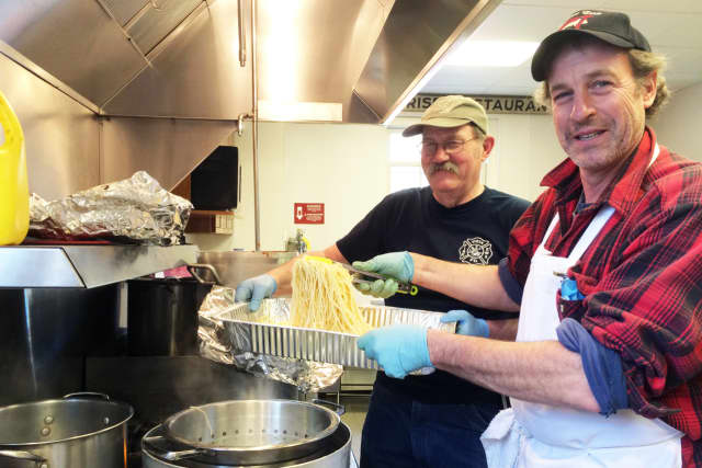 Volunteers Jim Hackett, left, and Joe Haberny cook at the Vista Fire Department's second annual Spaghetti Dinner.