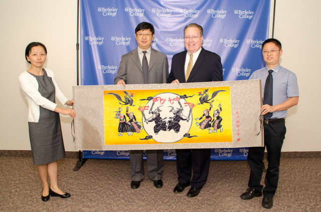 Yvonne Zhang, Chu Guangrong and Zhao Pu, of Guizhou University in China present this handmade gift to Berkeley College President Michael J. Smith, third from left.