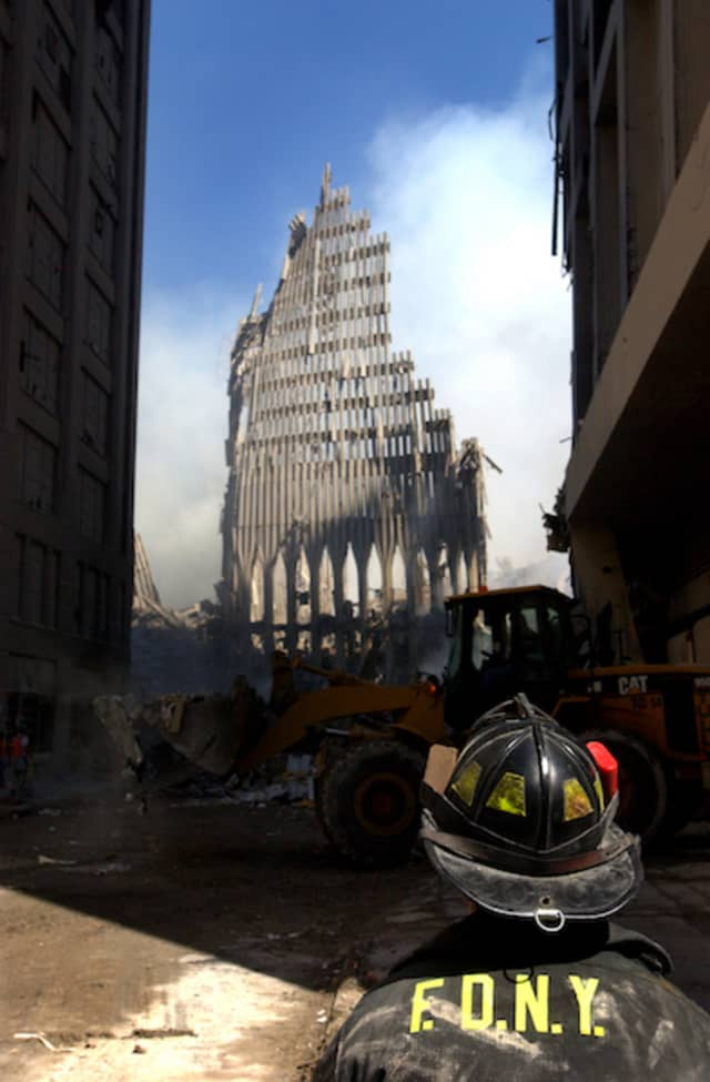 A New York City firefighter looks on at the skeletal remains of the South Tower.