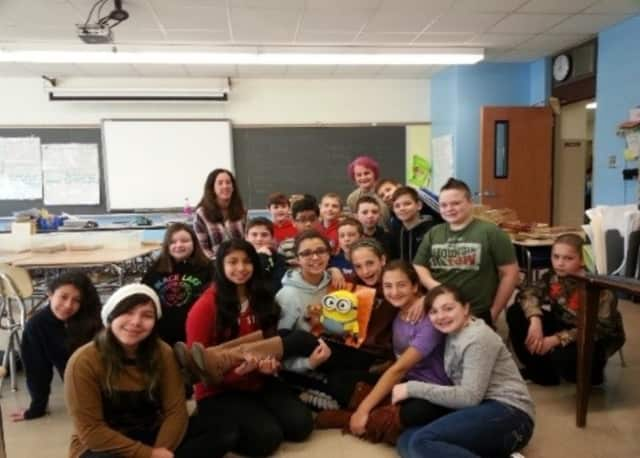 George Fischer Middle School sixth-graders conquered and surpassed the million page challenge by reading a total of 1,336,206 pages since the fall. The school Librarian, Elizabeth Krieger, back row, was so impressed, her hair turned pink.
