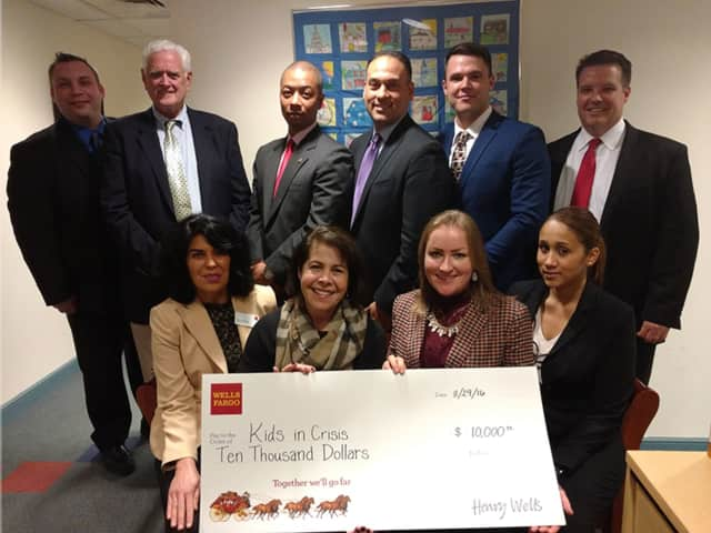 Greenwich Selectman John Toner joins employees from Wells Fargo and staff from Kids in Crisis for the check presentation.