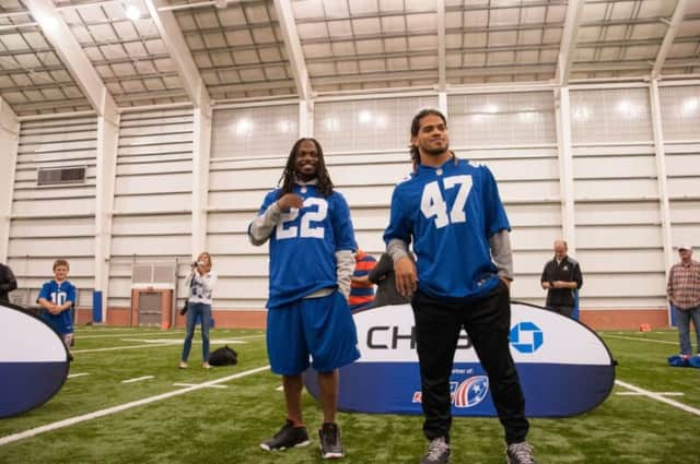 Giants linebacker Uani 'Unga and safety Brandon Meriweather. The Giants will have their annual Toys for Tots drive Dec. 20.