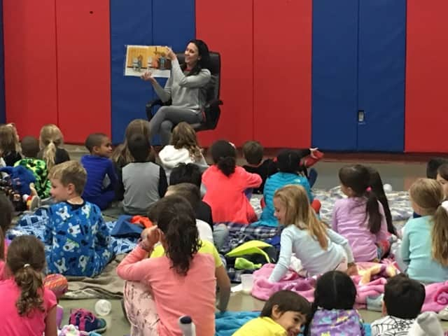"Children's book author Christina Geist reads ""Buddy's Bedtime Battery"" to children at the William B. Ward Elementary School's recent read-a-thon pajama party in New Rochelle."