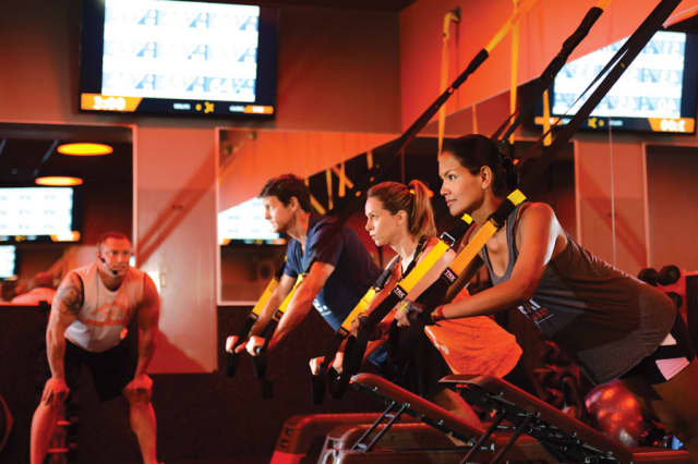 Orange Theory classes involve cardio and strength training. Clients use TRX suspension training to build strength. Photographs courtesy of Orange Theory White Plains.