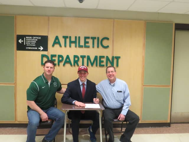 Yorktown High School senior Michael Rothman signs his academic scholarship to play baseball at Manhattanville College with his father, Allan, right, and coach Sean Kennedy, left, in attendance.