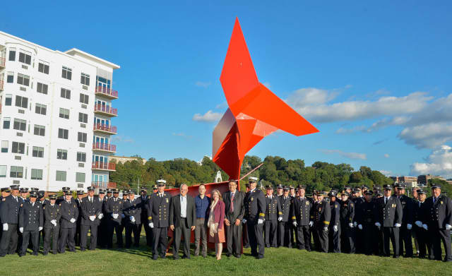 """Members of the Ossining Fire Department stand at Harbor Square around """"The Angel"""" sculpture at Sunday's dedication ceremony."""
